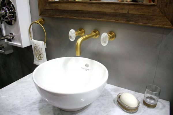 Minimalist bathroom sink with gold accents for faucets